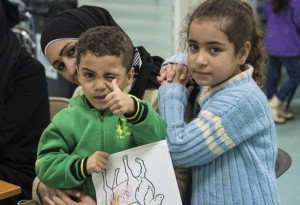 Two Syrian refugee children pose while their family undergoes medical screening before the beginning of an airlift to Canada, in Beirut