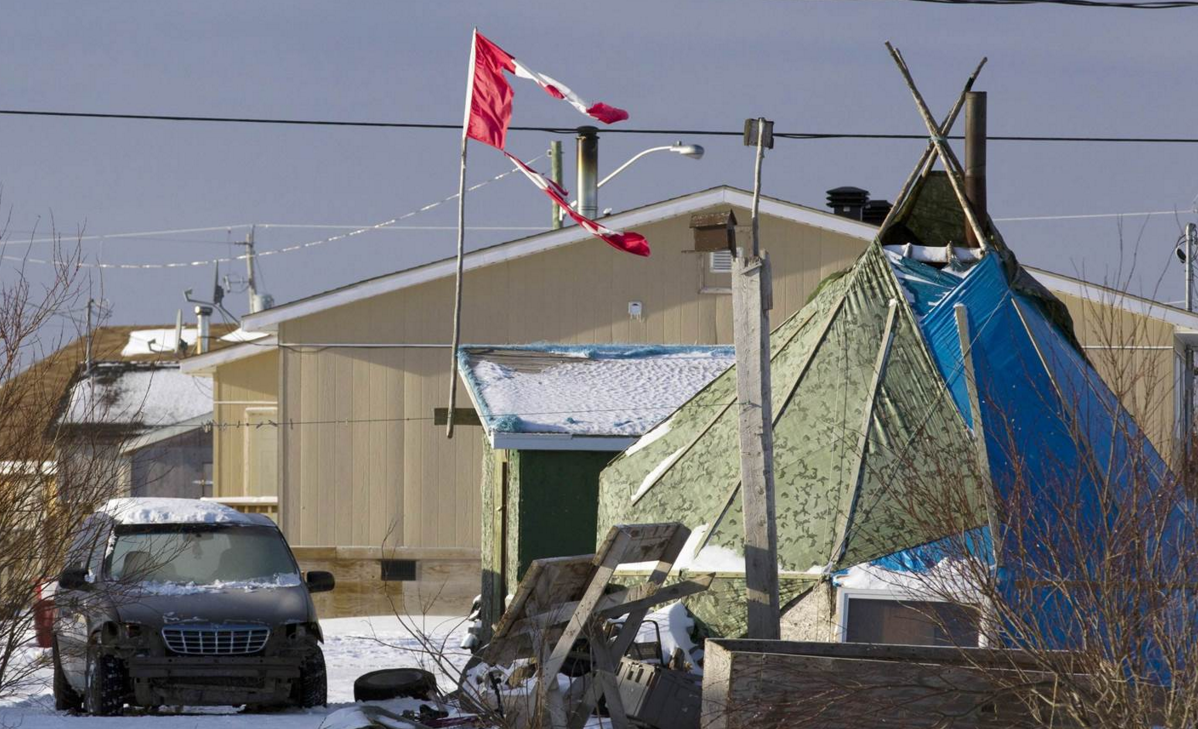 A shredded Canadian flag flies over a building in Attawapiskat, Ont., in November 2011.  (Adrian Wyld/Canadian Press)