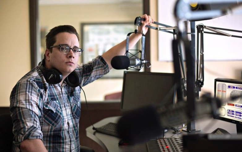 Andrew Wilcox, program director at 100.5 Cruz FM, pictured in Fort McMurray Alta, on Saturday June 4, 2016. From the streetfront window of rock station Wilcox can see the forested hill where his home still stands in the fire-scarred Abasand neighbourhood. THE CANADIAN PRESS/Jason Franson -
