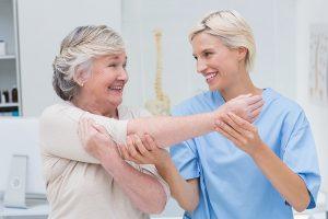 Happy nurse assisting patient in raising arm